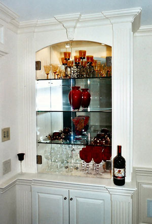 Glass doors in cabinet with shelves and mirror